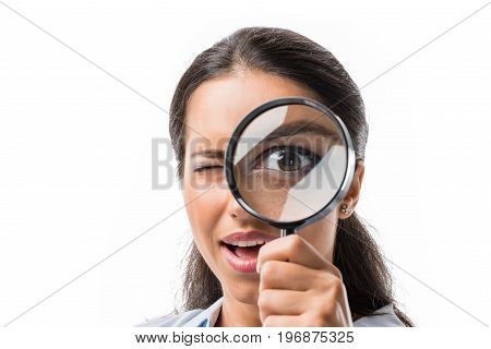 Portrait Of Businesswoman Looking At Camera Thorough Magnifying Glass Isolated On White