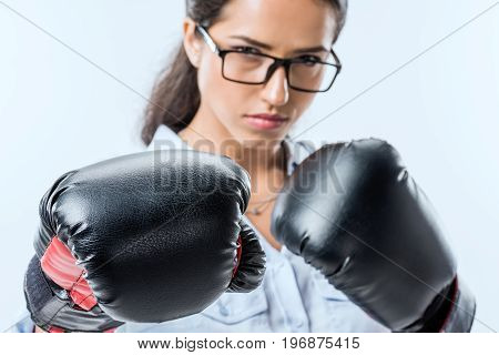 Portrait Of Serious Businesswoman In Boxer Gloves Looking  At Camera Isolated On Blue