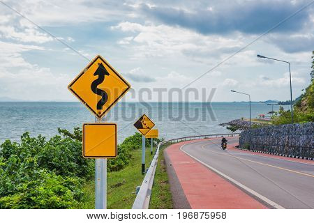 Yellow sign with winding road symbol in the countryside sea and sky background .