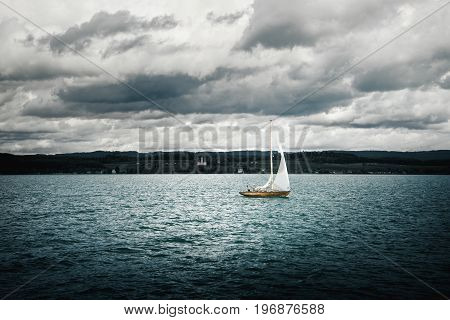 A sailboat in the water in front of beautiful landscape and dark cloudy sky