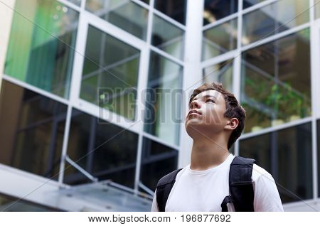 Stylish young man looks at business center windows