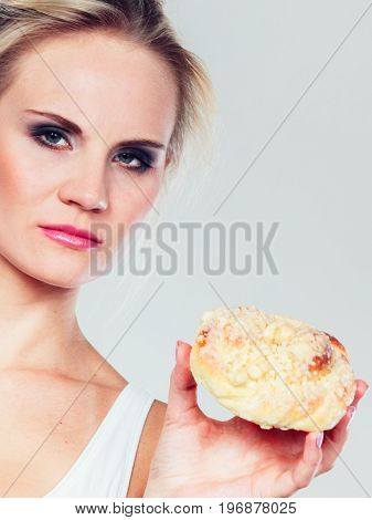 Undecided Woman Holds Cake Sweet Bun In Hand