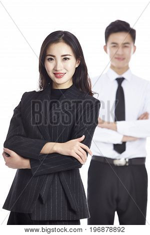 portrait of young asian businesswoman with male colleague standing in background studio shot isolated on white.