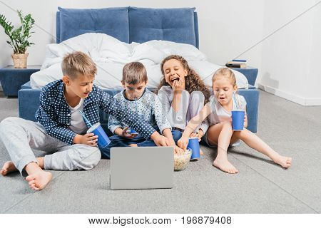Multicultural Children Resting And Watching Movie At Home Together