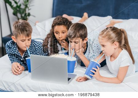 Multicultural Children Drinking Soda And Watching Movie At Home Together