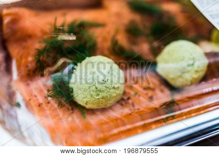 Raw Salmon Filets With Pesto Butter In Packaged Plastic Container