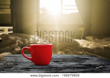 Hot drink in a red cup on grunge wood and Bed room blurred background