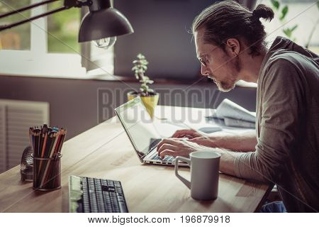 Freelancer typing and working with laptop. Man working on freelance at home seriously looking in computer.