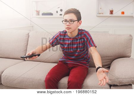 Teenager boy watching television, using remote control to switch channels. Youngster unhappy at what he sees on TV screen. Sitting on couch in living room at home