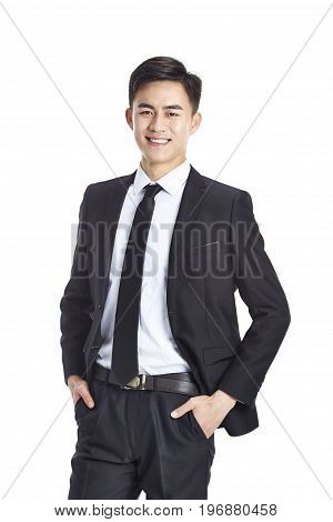 studio portrait of a young asian businessman in formal wear hands in pockets isolated on white background.