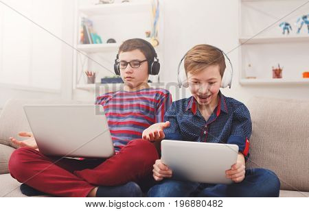 Technology, boy friendship and communication concept - two cute teenagers using tablets, playing games, talking and smiling while sitting on the couch in living room at home
