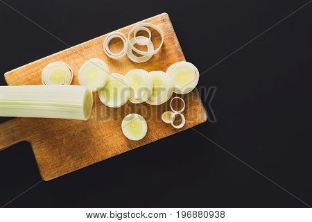 Cooking healthy food background. Cutting leek, fresh organic vegetables on wooden kitchen board at black. Natural food with copy space.