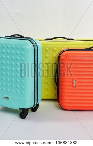 Bright suitcases for summer rest. Valises for clothes, white background.