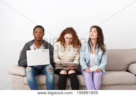 Young multiethnic students using gadgets sitting on couch indoors. Modern education technologies.