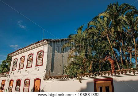 Overview of street with old houses and palm trees at the sunset in Paraty, an amazing and historic town totally preserved in the coast of the Rio de Janeiro State, southwestern Brazil