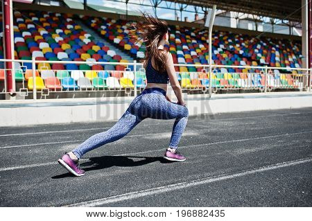 Portrait Of An Attractive Fit Woman Doing Exercises For Her Legs In The Stadium.
