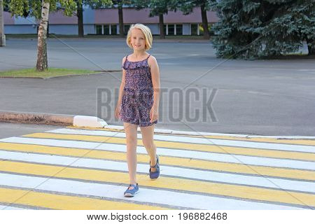 A girl of school age crosses the road on a pedestrian crossing