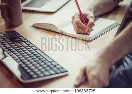 Close up view of freelancer hands writing with pencil in notebook. Man at wooden desk making sketches on paper.