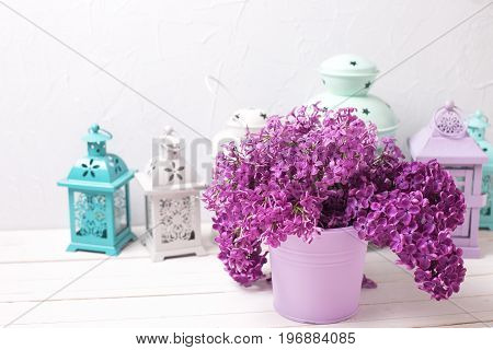 Lilac flowers and brigh lanterns on white wooden background against grey wall. Selective focus. Place for text.
