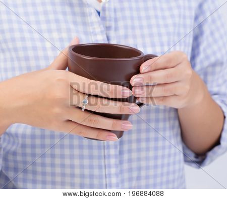 Female hands holding a brown cup of coffee