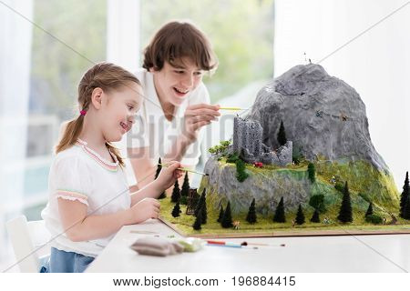 Children work on model building school project. Kids build miniature scale model mountain for geography class. Extracurricular activities and hobby club. Art and crafts for teenager and preschool.