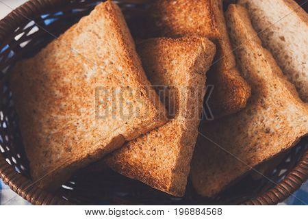 Breakfast background, white bread toasts in wicker breadbasket on checkered table napkin, closeup