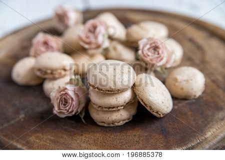 Close up beige French cookies macarons and dry roses for beautiful vintage background