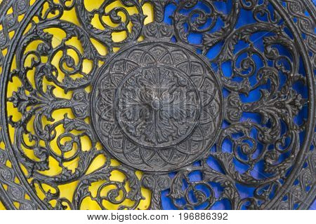 Part Of Openwork Cast-iron Plate On  Yellow And Blue Backgrounds. Top View.