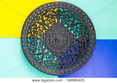An Openwork Cast-iron Plate On  Yellow, Green, Blue Backgrounds. Top View.