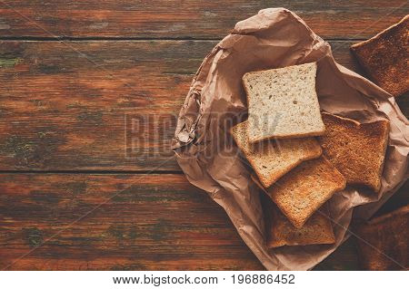Toasted slices of white bread in craft paper on rustic wooden table. Still life, top view, copy spase, bakery and grocery background