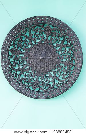 An Openwork Cast-iron Plate On A Neutral Green Background. Top View.