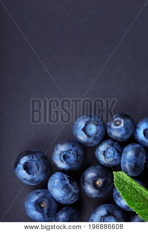 Top view of delicious and juicy blueberries with a green leaf of mint on a light blue background. Raw and ripe blueberries full of vitamins. Organic ingredients for nutritious summer desserts.