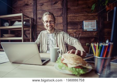 Freelancer man working at home going to have lunch break. Front view of young man sitting at working place, going to eat sandwich.