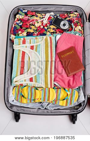 Woman clothes in opened suitcase. Passport, camera, sandals in traveler bag.
