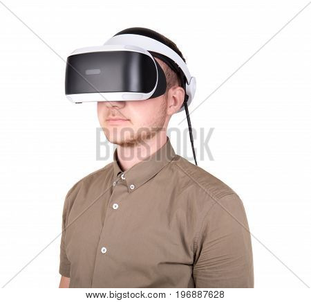 Close-up portrait of young man experiencing virtual reality, isolated on a white background. A man with professional virtual reality glasses. New reality video game. A guy in a virtual helmet.
