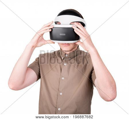 Close-up of a young man in a VR electronic devices, isolated on a white background. An attractive boy in virtual reality glasses. Professional and new audio equipment.