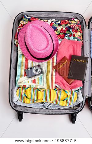 Open suitcase packed for travelling. Opened summer suitcase with personal things.