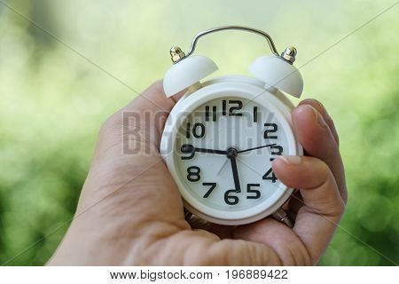 Closed up of white alarm clock in woman hand as business or time countdown concept with green bokeh background.