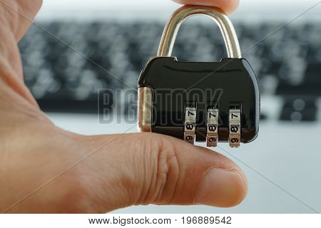 Computer security concept with hand holding combination lock pad with the background of computer keyboard.