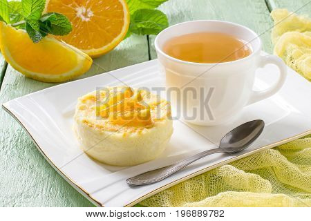 Delicious delicate orange dessert on plate and tea in cup. Pieces of oranges and mint on green wooden table with yellow gauze napkin