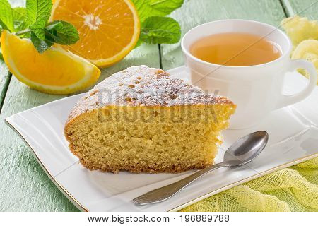 Delicious homemade orange pie on plate and tea in cup. Pieces of oranges and mint on green wooden table with yellow gauze napkin