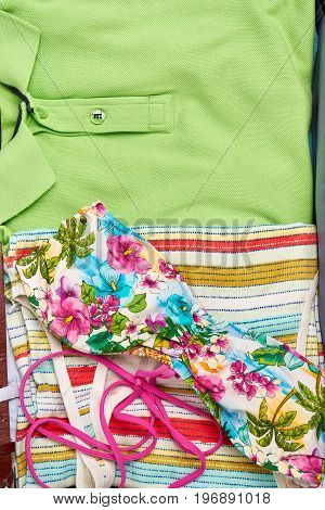 Summer colorful clothing macro. Man shirt and woman flowery swimsuit.