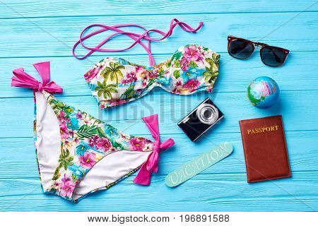 Swimsuit and accessories for going abroad. Colorful female swimsuit for rest in south.