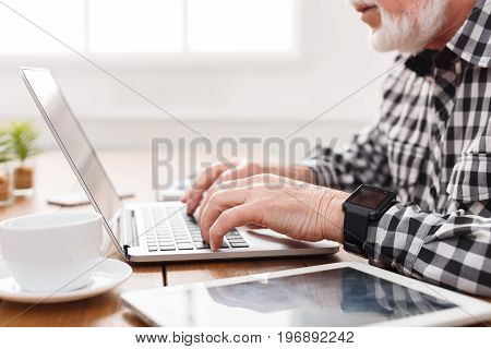 Senior male hands on laptop closeup. Unrecognizable bearded mature man typing on computer keyboard