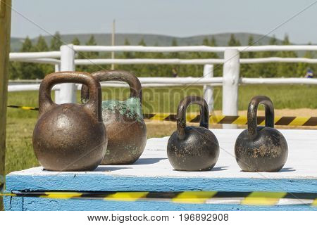 Iron weight on wooden platform. The background is blurred. Rustic background