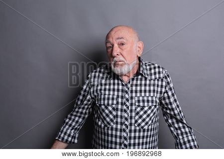 Portrait of unsure senior man looking confused, gray studio background
