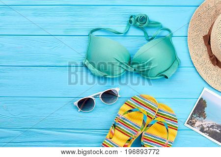 Sunbath clothing stuff for woman. Bra, hat, slippers, sea background.