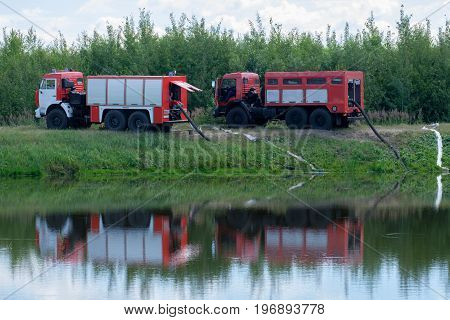 Two fire engines pump water from the pond