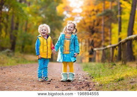 Kids Play In Autumn Park. Children In Fall.