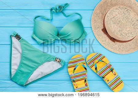 Modernswim suit, panama, slippers. Summer accessories on blue wooden floor.